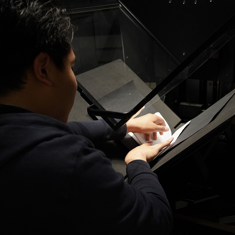 Employee Marco Perez digitizes 'The Selfish Gene' by Richard Dawkins as part of the Alternative Media Services program.