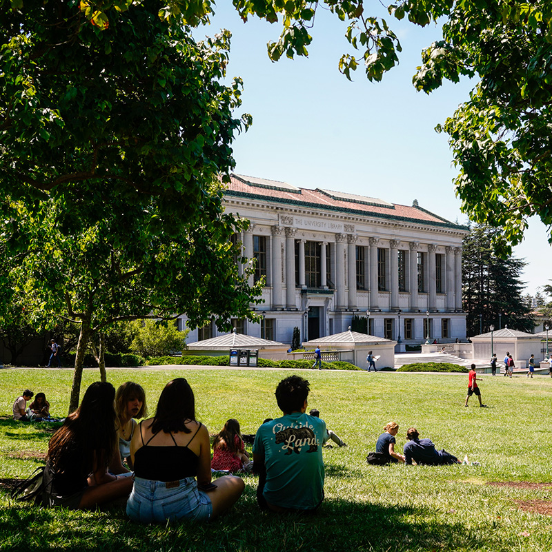 People relax on Memorial Glade with Doe Library in the background on a warm day during student orientation on Aug, 22, 2019.