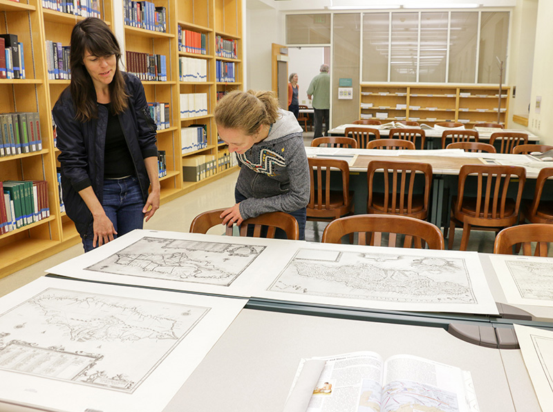 """History graduate students Nicole Viglini, left, and Amy O'Hearn discuss """"Hamilton, in Maps,"""" a pop-up exhibit in September 2017."""