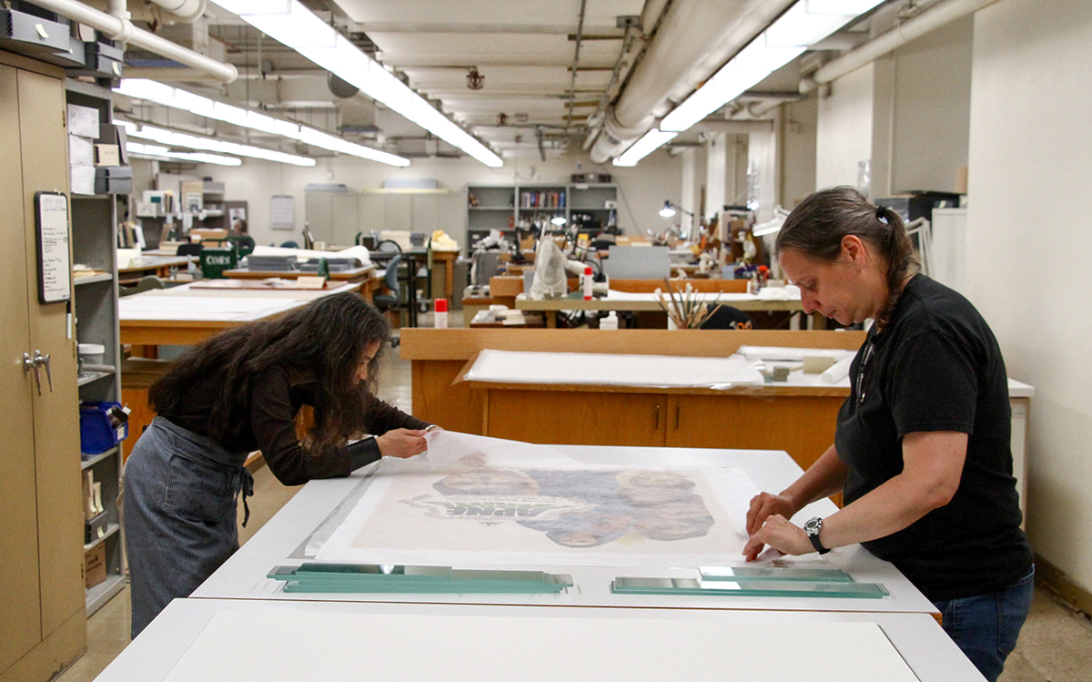 Library conservators Emily Ramos, left, and Erika Lindensmith, right, preserve posters in advance of a Bombay cinema exhibit at the Brown Gallery in Doe Library on Aug. 9, 2017. (Photo by Cade Johnson for the University Library)