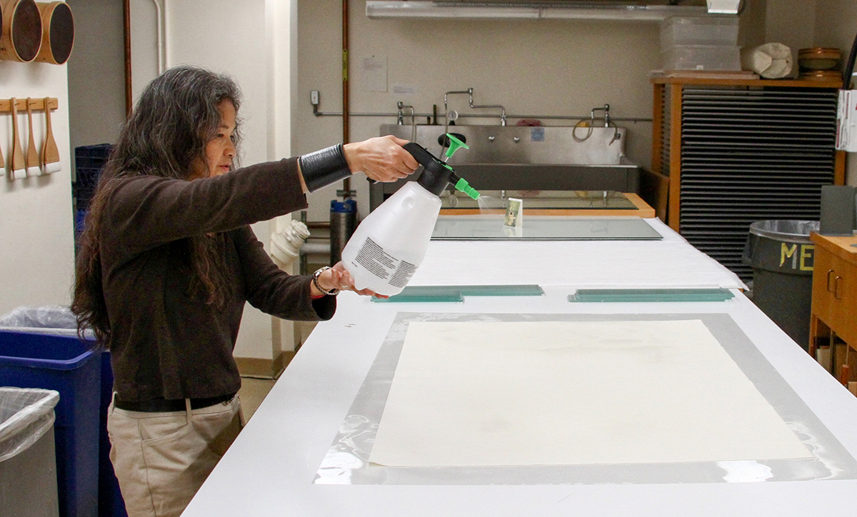 Library conservator Emily Ramos preserves posters in advance of a Bombay cinema exhibit at the Brown Gallery in Doe Library on Aug. 9, 2017. (Photo by Cade Johnson for the University Library)