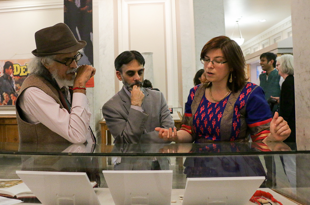 """Doctoral faculty member at the Institute for South Asia Studies Purushottama Bilimoria, left, and curator for South Asian Collections Adnan Malik, center, discuss displays in the """"Love Across the Global South"""" exhibit with co-curator Ivy Mills in Doe Library on Oct. 6, 2017. (Photo by Cade Johnson for the University Library)"""