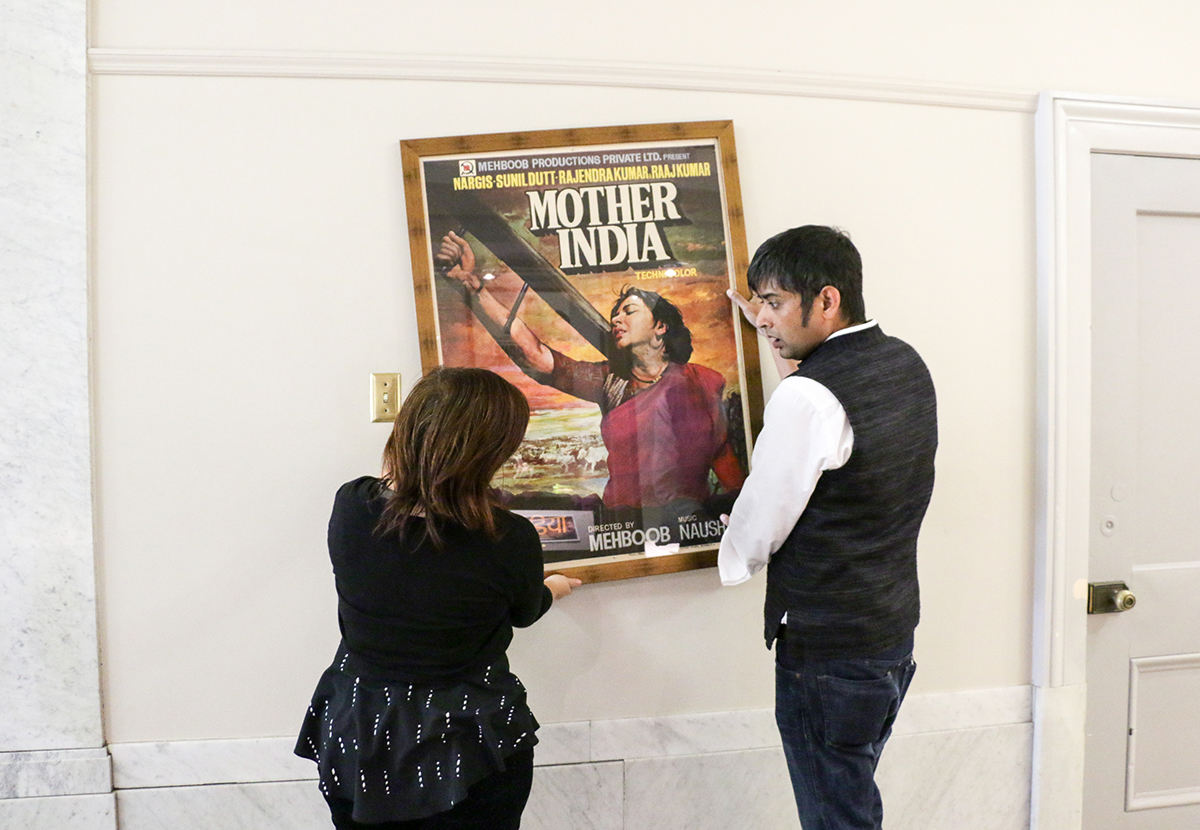 "Ivy Mills, left, a lecturer in the history of art department, and Sugata Ray, assistant professor in the history of art department, hang a framed poster for the ""Love Across the Global South"" exhibit in the Brown Gallery in Doe Library on Oct. 3, 2017. (Photo by Cade Johnson for the University Library)"