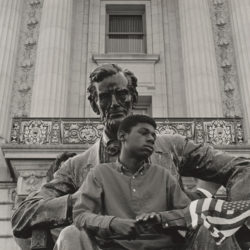 A boy sitting on the lap of a statue of Abraham Lincoln