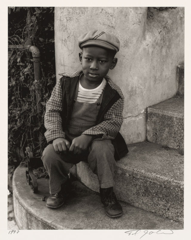 An African-American child sitting on concrete steps