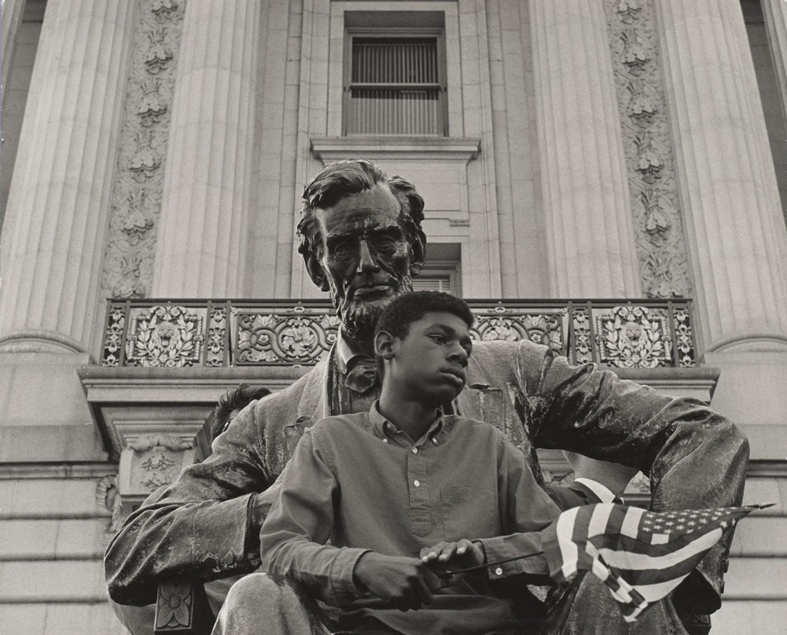 An African-American child holding a flag and sitting on the lap of a statue of Abraham Lincoln