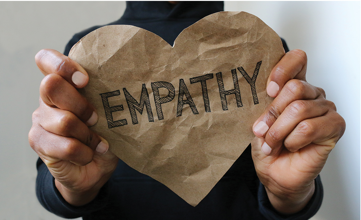 Two hands holding a paper heart that says 'empathy'
