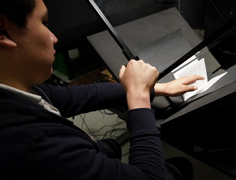 "Employee Marco Perez digitizes ""The Selfish Gene"" by Richard Dawkins as part of the Alternative Media Services program."